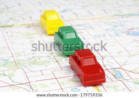 Plastic Toy Cars On Map - stock photo