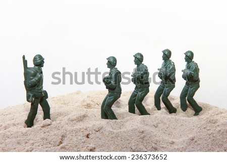 Plastic toy Soldiers with sand - stock photo
