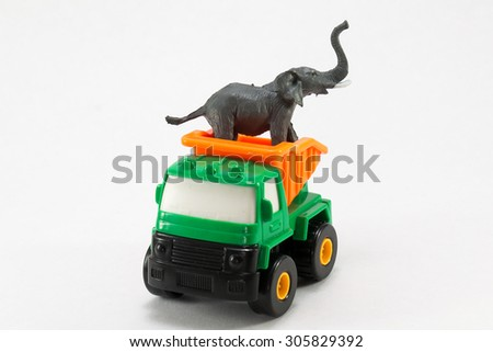 Plastic truck and elephant on a white background - stock photo