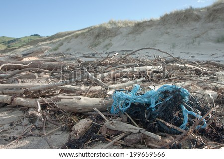 plastic twine twisted around driftwood littering a beach  - stock photo