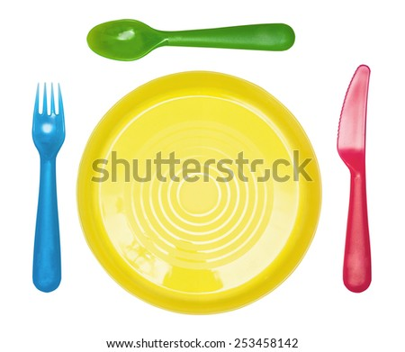 Plastic ware: a yellow plate, a blue fork, a green spoon, the red knife isolated on the white - stock photo