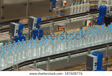 Plastic water bottles on conveyor and water bottling machine industry