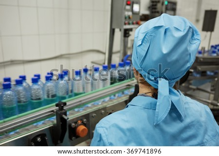 Plastic water bottles on conveyor and water bottling machine industry. Water bottling plant - stock photo