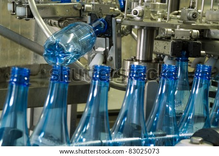 Plastic water bottles on conveyor or water bottling machine industry