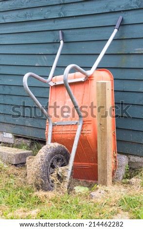 Plastic wheelbarrow leaning against a wooden shed - stock photo