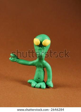 Plasticine figure of alien, on brown - stock photo