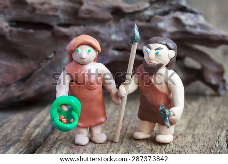 Plasticine world - a caveman with a spear and a stone ax and cave woman with a basket and berries, selective focus - stock photo