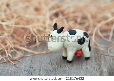 Plasticine world - little homemade black-and-white cow stands on a farm on background of hay, selective focus