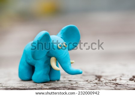 Plasticine world - little homemade blue elephant on a wooden background , selective focus and place for text - stock photo
