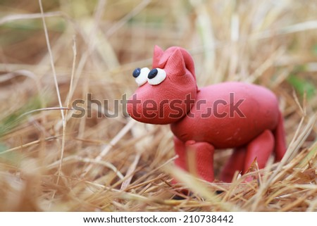 Plasticine world - little homemade red horse stands in the hay, selective focus on head - stock photo