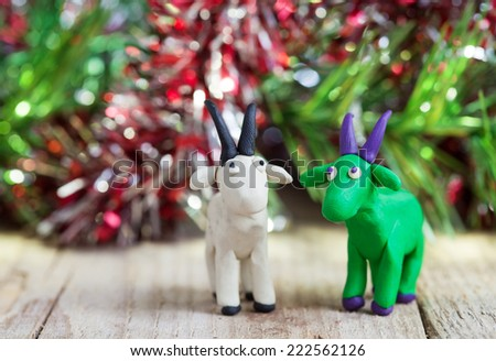 Plasticine world - little homemade white and green goat with purple horns and hooves stand on a wooden floor, selective focus and place for text - stock photo