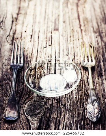 Plate a nd two forks on old rustic wooden table