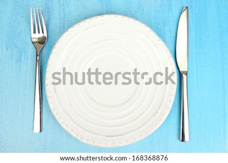 Plate and cutlery on wooden table close-up