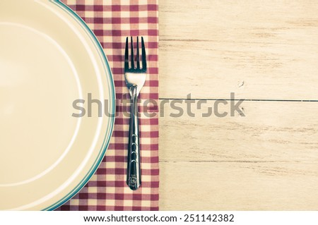 plate and fork with tablecloth on white wooden table and copyspace.