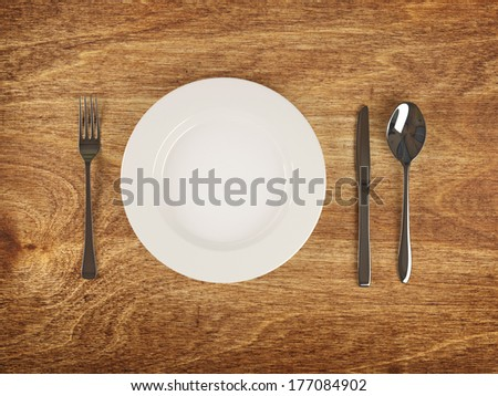 Plate and silver flatware on wooden table - stock photo