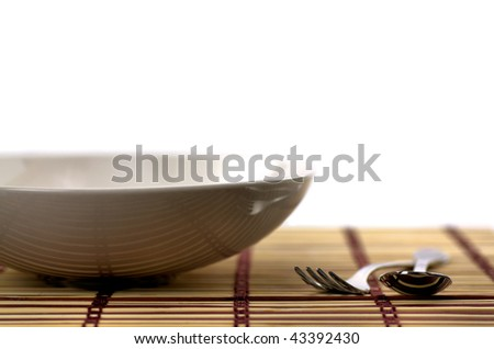 Plate, fork and spoon on table - shallow dof - stock photo
