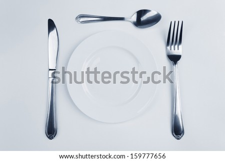 Plate,fork, knife and spoon on white background