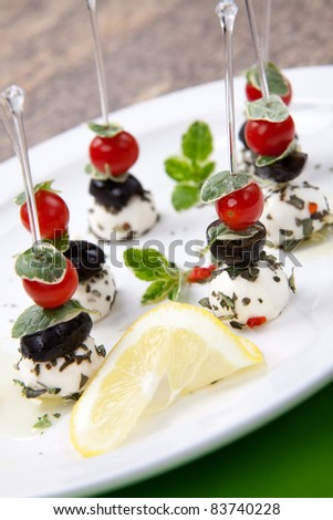 Plate full of delicious Mozzarella Cheese canape-sandwiches made from Mozzarella cheese, black olives, cherry tomatoes and oregano served with lemon