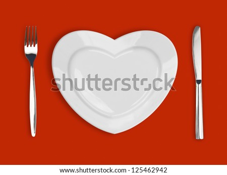 plate in shape of heart, table knife and fork on red background - stock photo