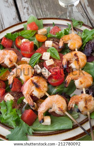 Plate of a grilled shrimp salad with feta cheese, tomatoes, and watermelon in a rustic setting.