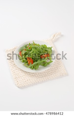 plate of arugula and tomato salad on white table mat