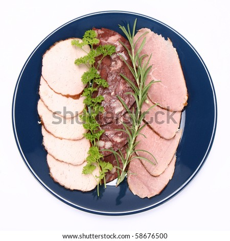 Plate of assorted cold cuts (ham, sirloin, headcheese) decorated with rosemary and parsley - stock photo