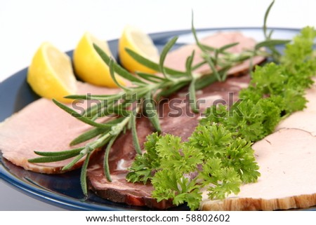 Plate of assorted cold cuts (ham, sirloin, headcheese) decorated with rosemary, parsley and lemon - stock photo