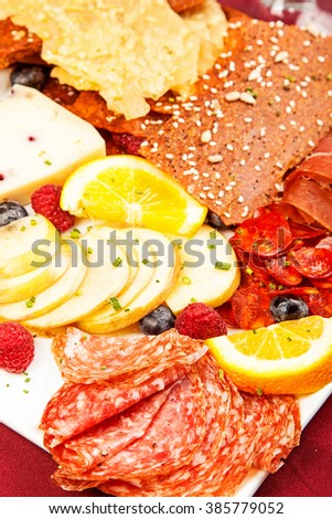 Plate of assorted meats, cheese, fruit and crackers