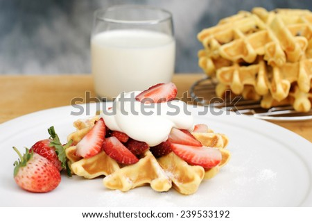 Plate of belgian waffles with fresh strawberries and whipped cream.  - stock photo