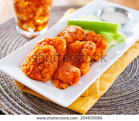 plate of boneless buffalo flavored chicken wings - stock photo