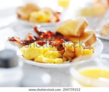 plate of breakfast food with bacon, eggs, toast, and fried potatoes - stock photo