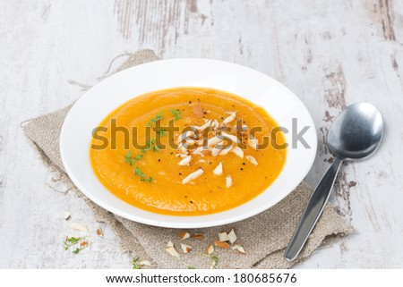 plate of carrot soup with almonds and watercress on white wooden table, horizontal - stock photo
