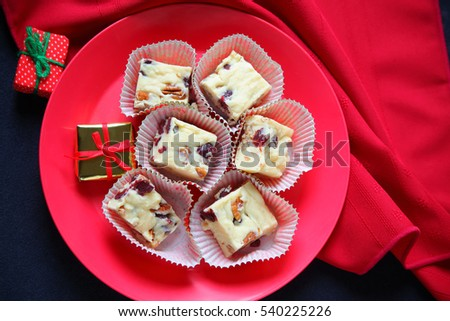 Plate of Christmas fudge made with white chocolate, cranberries and pecans with red napkin and miniature gifts