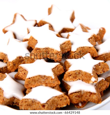 Plate of christmas star shaped cookies with white icing - stock photo