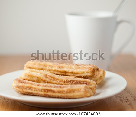 plate of churros and cup of coffee - stock photo