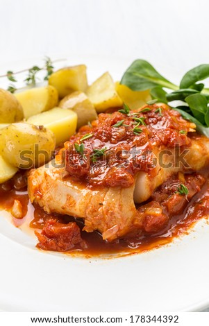 Plate of Cod or Pollack Fillet Braised in Tomato and Thyme Sauce Garnished with Boiled New Potatoes - stock photo