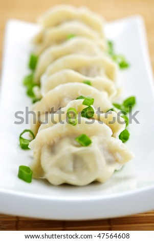 Plate of cooked chinese dumplings in a row - stock photo
