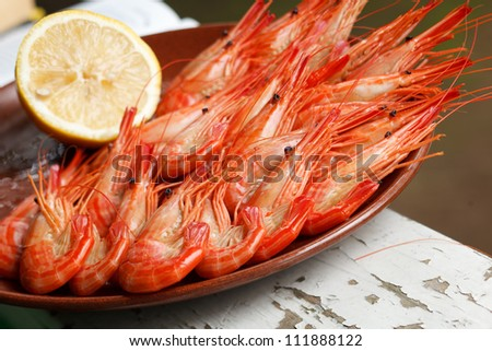 Plate of cooked prawns served with lemon on a rustic wooden table with peeling green paint - stock photo