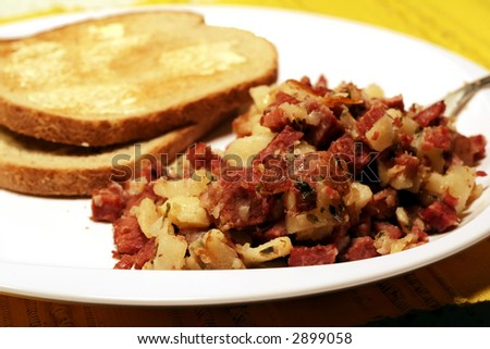 Plate of corned beef hash, potatoes, and buttered rye toast