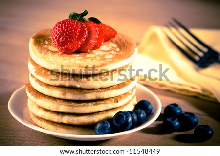 Plate of delicious freshly prepared pancakes with strawberry and blueberries - stock photo