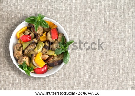 Plate of delicious grilled fresh vegetables prepared Turkish style with eggplant, zucchini and red and yellow sweet peppers, over head view on a beige cloth with copy space - stock photo