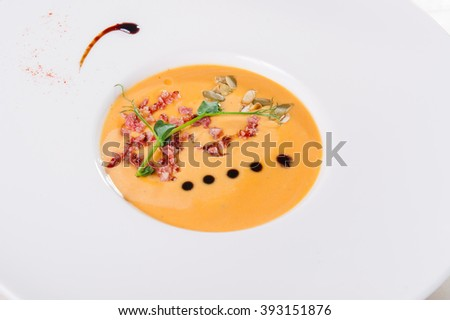 Plate of Delicious Pumkin Cream soup with bacon in the round white plate  on the served restaurant table