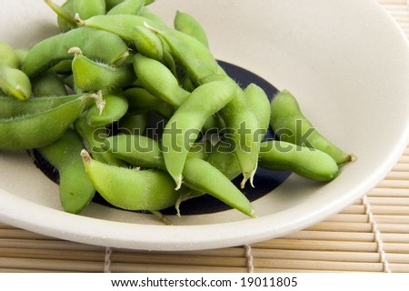 Plate of edamame on bamboo placemat - stock photo