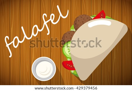 Plate of falafel with pita bread on wooden table. - stock photo