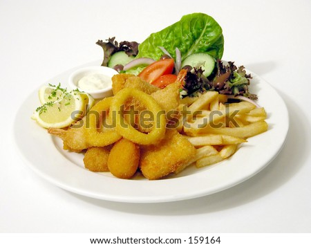 Plate of fish and chips and salad with sauce - stock photo