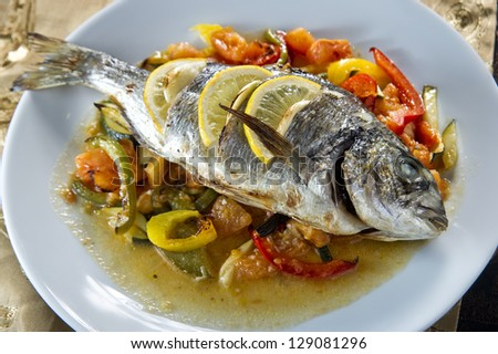 Plate of fish baked with vegetables. - stock photo