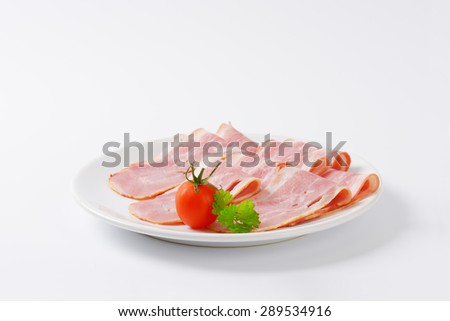 plate of fresh bacon slices on white background