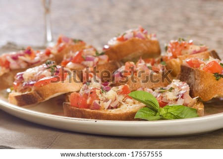Plate of fresh bruschetta with a sprig of mint - stock photo
