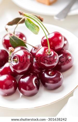 Plate of fresh cherries berries close-up - stock photo