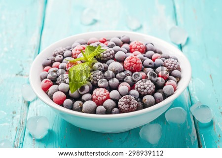Plate of fresh frozen berries on a turquoise background, closeup - stock photo
